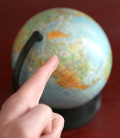 pointing finger on unsharp globe in backgrdound on wooden table photo
