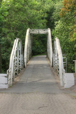 gray old iron bridge in the forest photo