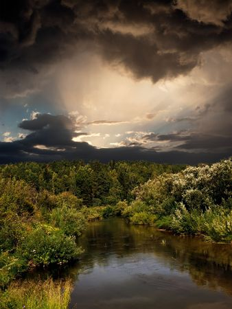 Evening landscape with dramatic sky and the river