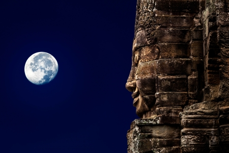 A stone sculpture of Buddha on the background of the night sky and the moon