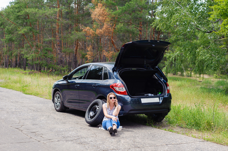 calling for help: Young beautiful sexy woman at broken car with mobile phone, standing in the public road in forest area, calling for help with mobile phone. Broken vehicle in the background.