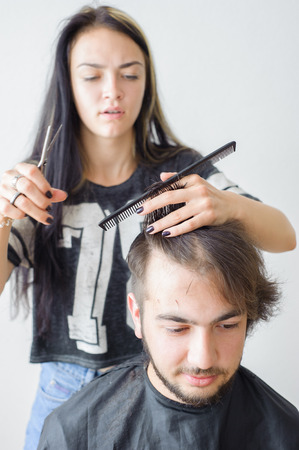 haircutting: Mens hairstyling and haircutting in a barber shop or hair salon.
