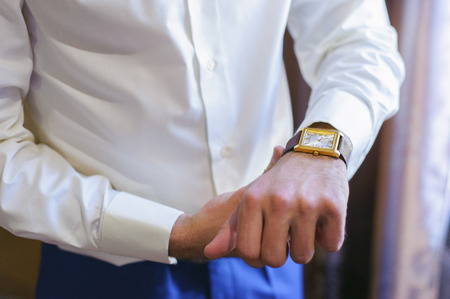 cuff link: A man in a white shirt straightens his cufflinks