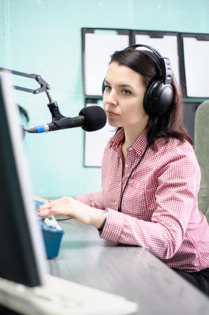 radio dj: A radio DJ announces news in a radio-studio
