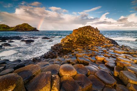 Sunrise view at Irish giant causeway vulcanic formation with rainbow nearby Stock Photo