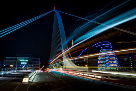 Harp bridge in Dubliny with cars passiing through by night Фото со стока