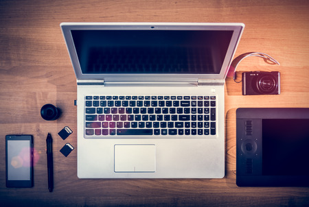 postproduction: Workplace of phrographer. Laptop, pen tablet, SD Cards, smartphone and compact camera. Postproduction and digital editing concept.