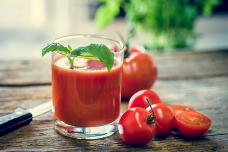 A glass full of tomato juice a few small tomatos in on the wooden table