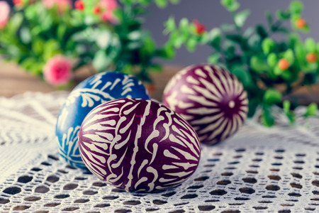 fancywork: Hand-painted easter eggs, colorised, on the wooden table and embroidered napkin