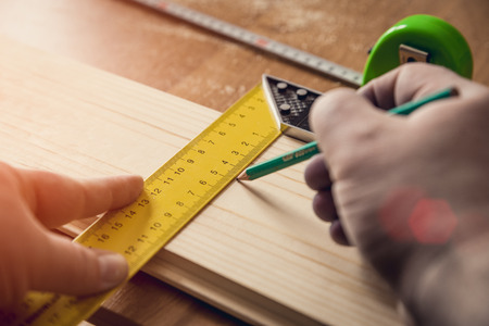handtools: Carpenter measuring wooden board with setsquare and tape-measure