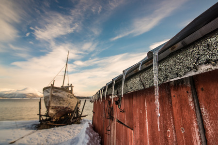 Icicles and old wreck boat, by the lake in winter. Norway Stock Photo