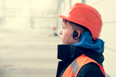 10 years old caucasian boy in safety helmet and reflective vest. Young engineer concept. Stock Photo