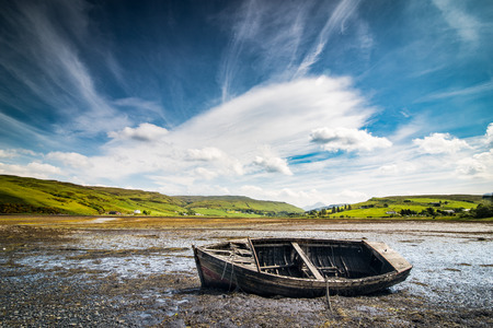 Old wreck fishing boat lying on the dry bottom of the sea during outflow Stock Photo