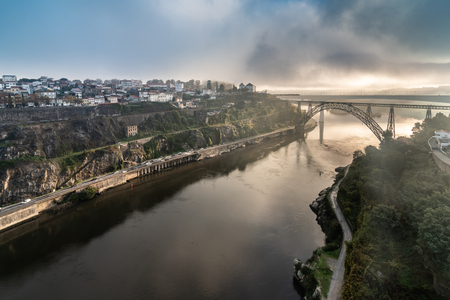 Distant view of the D. Maria Pia and Sao Joao Bridges, in Porto, Portugal during the morning hour. Cloudy sky.