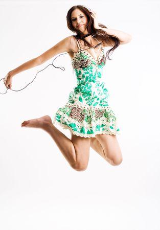 actief luisteren: Jonge vrouwelijke springen tijdens het luisteren naar muziek