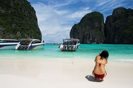 photographing: Girl photographing tropical beach with boats