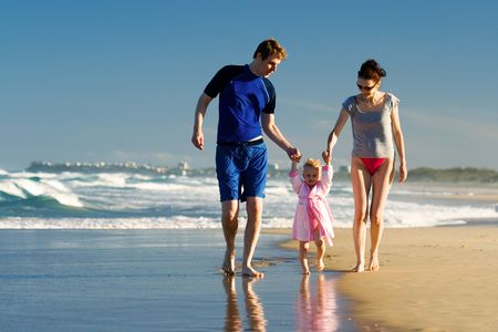 Young family walking on the beach photo