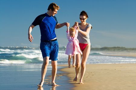 carying: Young  carying the child on the beach Stock Photo