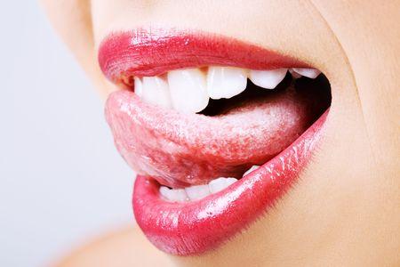 舌: 彼女の赤い唇をなめる若い女性の詳細