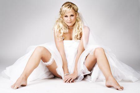 Sexy bride showing garter on the floor