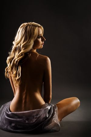 tanned body: Blond with bare back after shower isolated on black