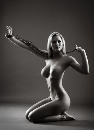Attractive nude female with snake in her hands photo