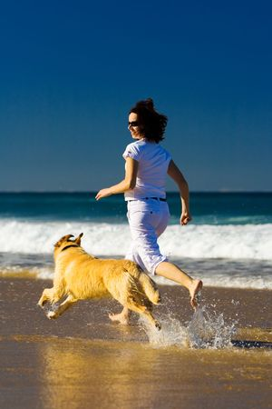 frienship: Young woman running on the beach with dog