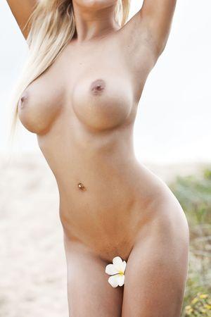 nue plage: Corps de femme nue sur la plage, la tenue des fleurs Banque d'images
