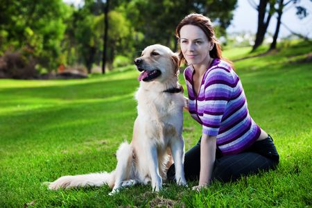 Young woman and golden retriever sitting in the grass photo