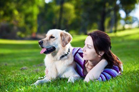 mujer con perro: Mujer joven y golden retriever acostado en el pasto