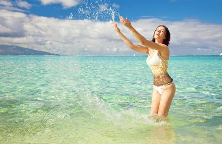 Young woman having fun splashing water in tropics photo