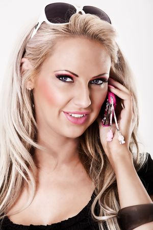 Beautiful blonde woman with pink makeup talking on phone photo