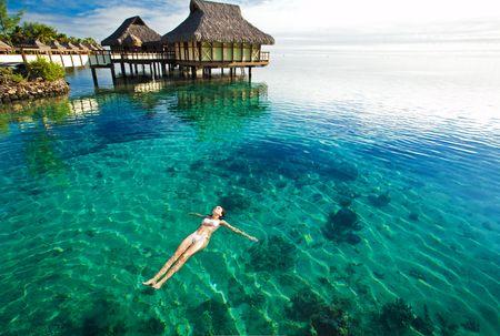 moorea: Young woman in white bikini swimming in a coral lagoon