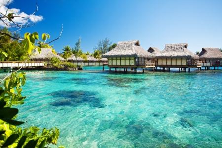 Over water bungalows met over amazing groene lagune Redactioneel
