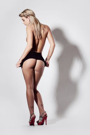 Slim nude woman with great butt in heals Stock Photo