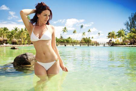 moorea: Young woman in white bikini standing next to tropical beach Stock Photo