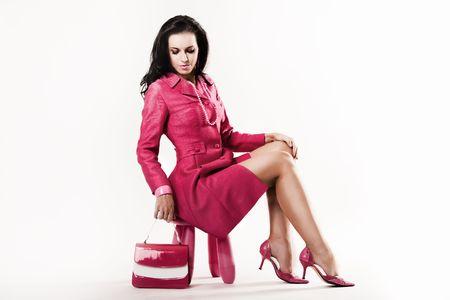 すべてピンク座っている身に着けている洗練されたセクシーな若いモデル