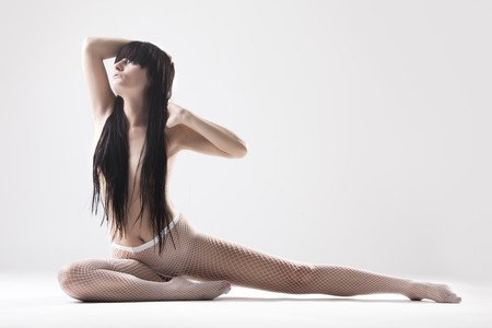 Young slim woman dressed in white fishnet stockings stretching Stock Photo - 6965631