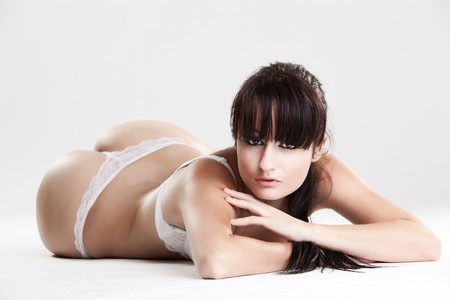 Female model in white lingerie laying on the ground isolated Stock Photo - 6965632