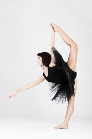 Beautiful female ballerina doing split against white background  photo