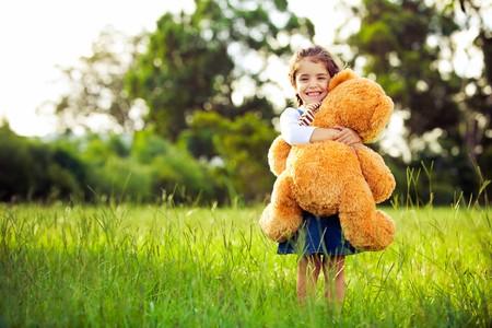 Niña bonita de pie en la hierba sosteniendo el gran oso de peluche