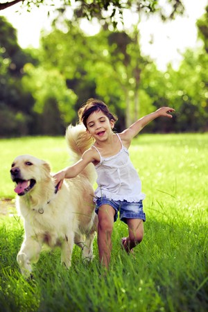 Young girl with golden retriever running outdoors photo