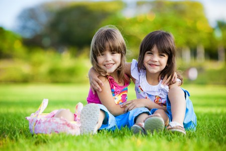 sibling: Two young smiling girls hugging each other in the grass