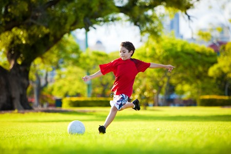 kids feet: Young excited boy kicking ball in the grass outdoors