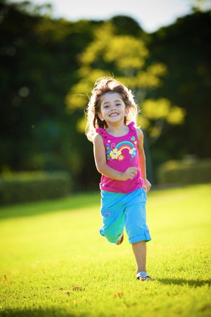 the runs: Young excited and smiling girl running in the sunlit grass Stock Photo