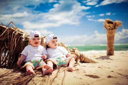 identical twin boys relaxing on tropical beach Stockfoto