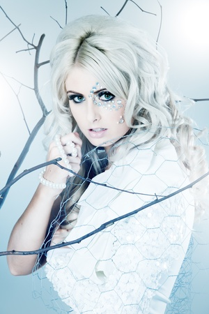 Blonde young beautiful woman dressed as winter queend photo