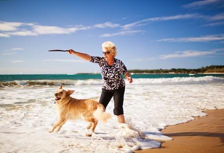 Mujer feliz jugando en la playa con golden retriever