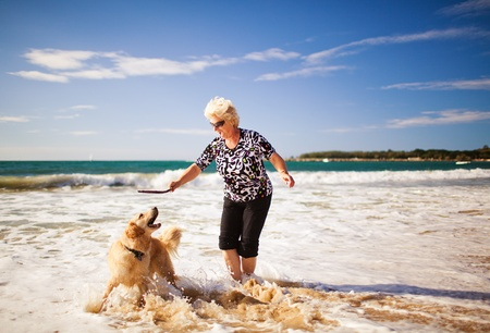senior friends: Happy woman playing on the beach with golden retriever