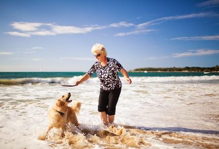 perros jugando: Mujer feliz jugando en la playa con golden retriever